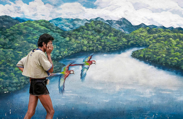 A man walks along a street in the city of Tarapoto, in front of a mural depicting the majesty of the Amazon.