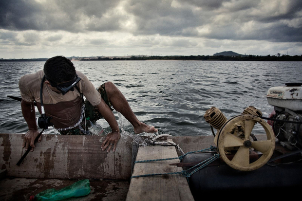 A fisherman climbs upon his boat after being fishing underwater. The kind of ornamental fishes that he catches are going to be extincted after the damming of the Xingu.  © Dario Bosio/Parallelozero