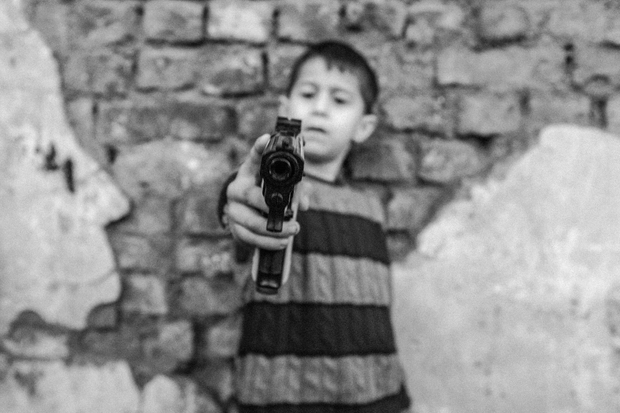 Syrian child is pointing a toy gun.
