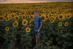 Sunflowerboy. At home in a valley of sunflowers, the young boy Benjamin Gradinari spends a lot of his time working and playing. It's strikingly beautiful and a big contrast to life itself. Moldova's poverty and lack of jobs forces families to be apart in search of a better life. Finalist, LensCulture Exposure Awards 2015.
