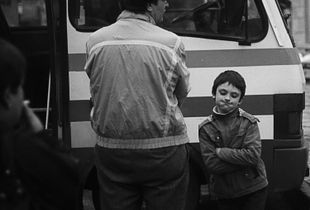 A boy with his dad at the bus station.