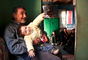 © Nada Elissa - Amo Ahmed entertaining little Nonna while she looks at me and embraces her family sitting at the back of the room.