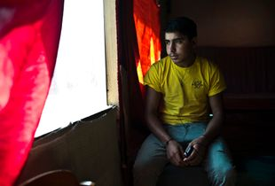 Afghan minor listens to music in the Jungle Book Cafe