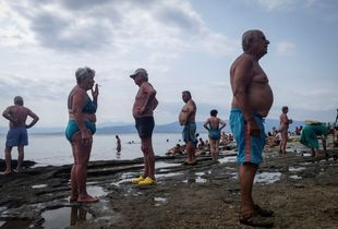 Tourists enjoy the sun on the shores of the Aegean Sea after swimming in Greece, August 2017.