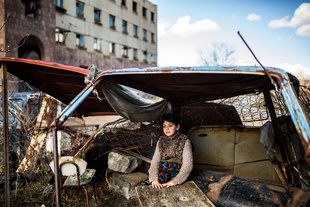 "Syuzanna (9) sitting in a ""shelter"" made of old car rusty parts. Ten days ago Syuzanna's father committed suicide, as people say, because of debt."