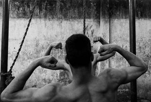 Imitation. A couple of lads showing off their muscles just before their wrestling match. © Swarat Ghosh. Finalist, LensCulture Street Photography Awards 2017.