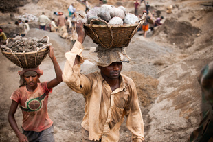 Quarry labors carrying stone to trucks
