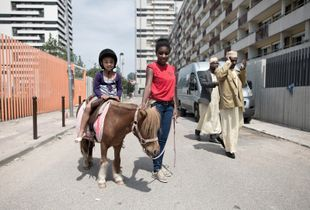 That day is the block party, organized by a local association. Youth of the neighborhood helps to regulate the various activities: pony, stilts, african braids stand, parades... The party will end when a drunk man will threaten some youth with a stick. © Hugo Aymar