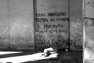 A homeless man sleeps under arcades; 2011