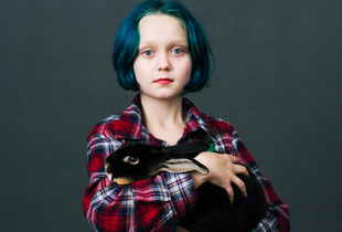 "Virginia Anderson (10) from Dallas, Oregon stands with her bunny Romeo (6 months). He is a ""Black Otter Rex"" breed and was just bought at the show."