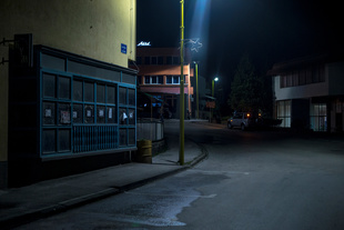 Srebrenica, From Night to Night. An empty street in the small downtown of Srebrenica in Bosnia. On the windows of an abandoned shop, death notices are displayed. A streetlight illuminates a neon star-shaped that no longer works. © Adrien Selbert. Chosen for the LensCulture Street Photography Awards Top 100.