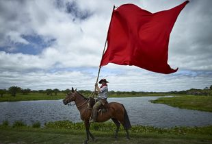 Gaucho flying the Gauchito Gil red coloured flag in the El Yaguarì estancia in Curuzù Cuatià village