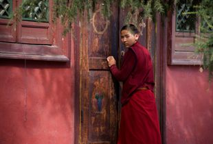A Mongolian Monk Gives A Watchful Eye At Gandan Monastery