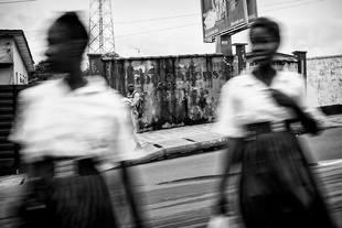 Two Girls are crossing the street in Freetown, Sierra Leone.  The walls are covered with writings of awareness: Ebola Stops With Me.
