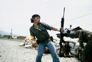 """Sandinistas at the walls of the National Guard headquarters: """"Molotov Man,"""" Estelí, Nicaragua, July 16, 1979 © Susan Meiselas / Magnum Photos. Courtesy Thames and Hudson."""