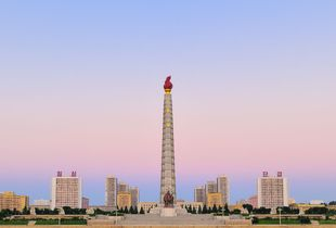 Juche Tower in the centre of Pyongyang surrounded by symmetrical, communist style architecture.