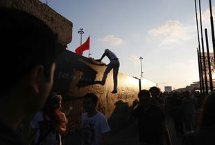 A protester tries to jump over the fence of the former Atatürk Cultural Center during a demonstration in Taksim square in Istanbul on Saturday, June 8 2013.