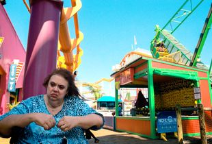 A woman sits on the padded seat of her rollator walking aid between the West Coaster and Sea Dragon rides. Pacific Park is an oceanfront amusement park, located on the Santa Monica Pier. It is the only fun fair on the West Coast of the United States situated on a pier and is LA's  only admission-free park.