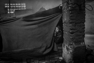 A young boy wakes up in his tent inside the barracks