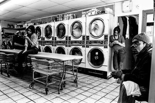 Man, watches television in a Laundromat while three women are on their cell phones.