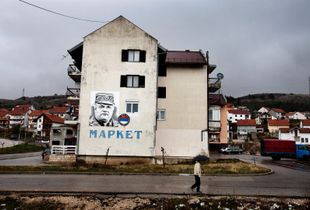 A pedestrian passes in the rain a mural of General Ratko Mladi?, currently indicted by the International Criminal Tribunal for the former Yugoslavia (ICTY) in The Hague. In many areas of the Republika Srpska war criminals are considered as heroes among the civilians. ©Ole Elfenkämper