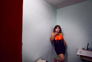 Reyna Patricia is enjoying a cigarette in his kitchen. He works as an is a transsexual prostitute in Play Del Carmen, Mexico. © Meeri Koutaniemi