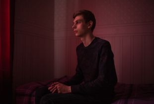 """Sasha, 22 years old, poses for a portrait at his apartment in St. Petersburg, Russia. Sasha says: """"I am the only son of my parents. If I tell them that I am gay, I will get nothing for myself, but they will be absolutely devastated. All sense of their life... just bang! … it will get rotten."""""""