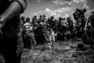 A young boy from Afghanistan disembarks from a boat after arriving on a beach at the north part of Lesbos island, Greece, coming from Turkey on the 10th of June 2015.