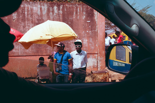 """Yellow and blue"", Bissau, Guinea Bissau. Two friends wait for public transportation. In Bissau, buses are yellow and blue."