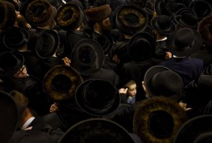 Waiting to Catch a Glimpse of the Rebbe. A young Orthodox Jewish boy surrounded by hundreds of Orthodox Jewish men wearing black coats and hats. The men are gathered to see their spiritual leader who has arrived from Antwerp. Finalist, LensCulture Portrait Awards 2015.