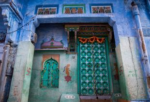 "A house in the ""blue city"", with beautifully adorned walls and door -- colors are everywhere!"
