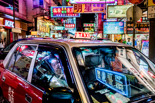 China Psychedelic: Neon Taxi. These red-and-white cabs are ubiquitous on the congested streets of the city. I tried to fill the frame with the taxi and the neon signs in the background and also on the windshield. © Jon She. Chosen for the LensCulture Street Photography Awards Top 100.