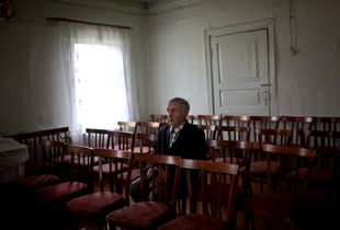 Bekk Villi Oskarovich sits in the Lutheran church after Sunday mass in Syktyvkar, Russia. He was held in captivity in a labor camp for years. He is originally from Ukraine, but lives in Syktyvkar, Russia. Finalist, LensCulture Portrait Awards 2015.