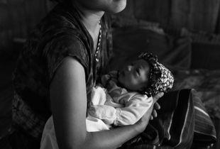 Newborn Karen child in Myanmar, born stateless in a refugee camp
