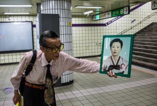 Man showing a photo of his wife and asks people passing by if they have seen her. Seoul, South Korea.