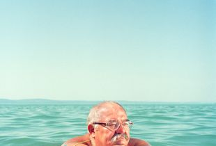 A man swims in Lake Balaton wearing an old wallet, a typical accessory in the 1970s.