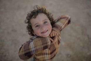 Syrian refugee boy in an informal tented settlement in Jordan.