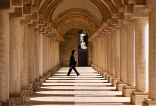 An ultra-Orthodox Jewish man walks past an archway at the YMCA building in Jerusalem