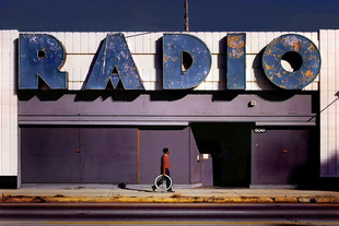 A powerful graphic sign on a mid-city Los Angeles building is complemented by the passer-by in the red sweater, sporting a bike tire. 3rd place, Single Image, LensCulture Street Photography Awards 2015.