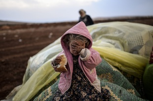 Near the southeastern town of Suruc, Sanliurfa province, Turkey, October 2, 2014. A Kurdish woman and her daughter wait after crossing from Syria into Turkey, with mortar fire on both sides. © Bülent Kiliç / AFP