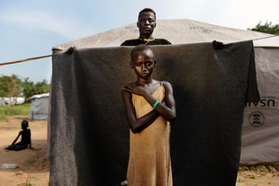 """Anoel, ± 7 years old, lives in the internally displaced persons camp """"Milkman"""" in South Sudan. """"I don't know my age. I think I am seven years old, but it's not important. I don't feel safe, especially when I think of all the violence I saw. I am also afraid that people will think less of me because I am wearing a shirt that doesn't really cover my body."""