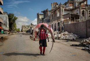 A man carries a huge hammerhead shark through the streets of Mogadishu.
