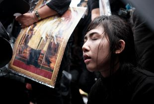 Thai girl exhausted during mourning after death of King Rama IX.