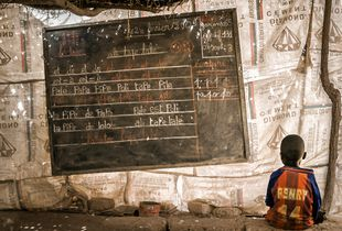 A kid sitting on a concrete bench on a school in the slums of Ouagadougou (Burkina Faso)