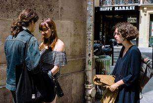 On Rue de l'Éperon, a couple share each others gaze while a friend looks on holding a jacket.