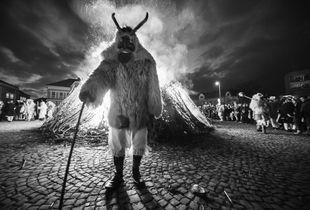 Morose busó standing against the fire.
