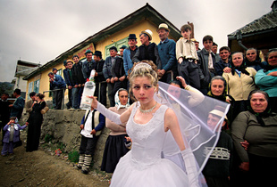 The Vodka Bride. Wedding in Maramures, Romania. In this very traditional county, a bride offers a shot of liquor to the people. The couple is working in the EU but they came home for the wedding. © Vasile Dorolti. Chosen for the LensCulture Street Photography Awards Top 100.