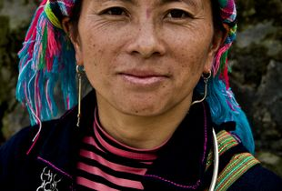 H'mong Lady wearing the traditional  brightly coloured scarf wrapped around her head and heavy silver jewellery.