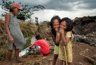 Children manage to playfully pose for a shot despite the dismal condition on Smokey Mountain.