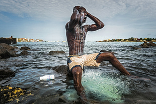 Kherou Ngor, a young wrestling champion, washes himself with milk at the shore of Ngor. He performs this ritual in order to obtain the reinforcements of a ghost who lives in the stones at the shore.